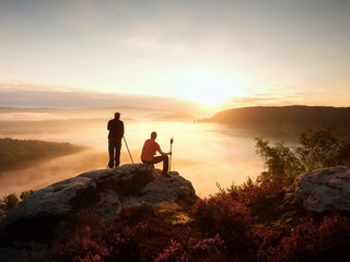 Hiker and photographer with tripod on rock and takes photos. Dreamy fogy landscape,