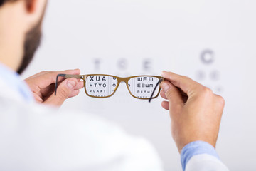 optician holds glasses in front of eyesight test chart