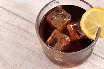Cola drink with ice cube and lemon slice on white rustic wood background top view