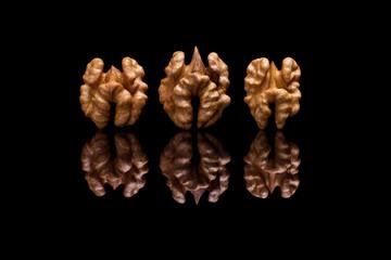 Three walnuts on black background
