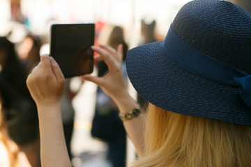 Woman in blue hat takes picture on her tablet