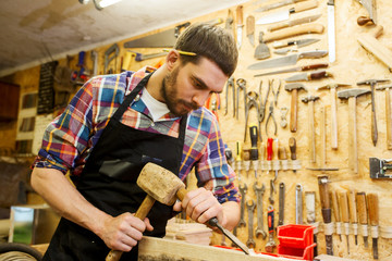 carpenter with wood, hammer and chisel at workshop