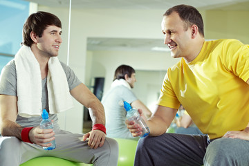 Two men communicating at gym while resting