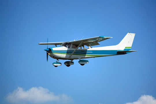 Light general aviation aircraft on final with cloud sky landing configuration