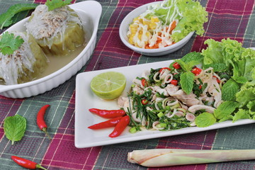 Spicy and sour mixed herb salad with pork and chicken  with side dish as mini vegetable salad and streamed gourd  wrap vermicelli and pork in soup. Selective focus