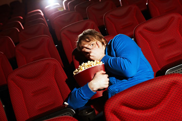 Young man watching horror film in cinema hall
