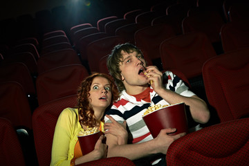 Young girl sitting terrified at cinema hall, her impassive boyfriend eating popcorn