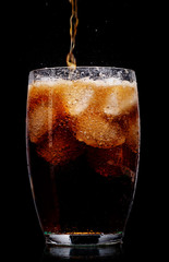 Glass of cola with ice on black background.