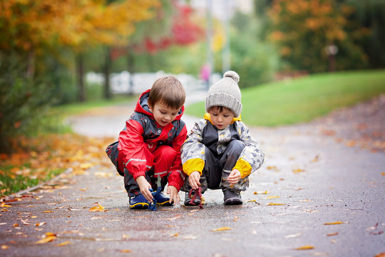 Two children, playing with toys in the park on a rainy day