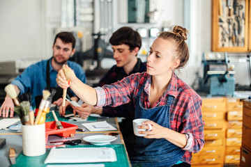 Young craftswoman holding coffee cup and reaching out for paintbrush in creative print studio, with two young craftsmen working in background