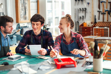 Young craftswoman holding brush and laughing and smiling with two young craftsmen in creative print studio