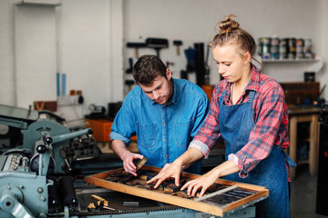 Man and woman working together in printing shop