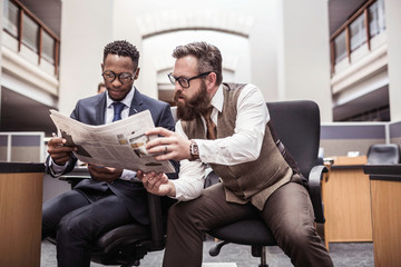 Two businessmen reading broadsheet newspaper in office