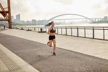 Woman jogging on riverbank in urban area, South Bund, Shanghai, China