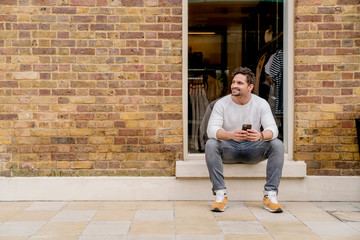 Young man with smartphone sitting on doorstep, Kings Road, London, UK