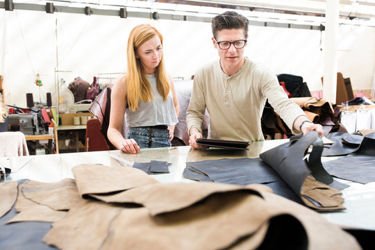 Male and female colleagues working together in leather jacket manufacturers