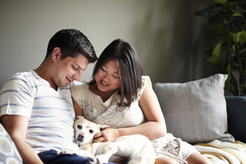 Mid adult couple relaxing on sofa with dog