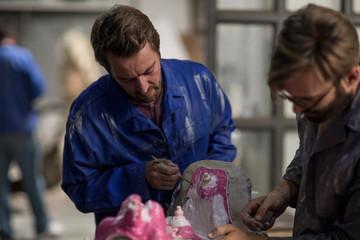Sculptors in artist studio creating plaster cast sculpture