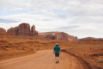 Rear view of young man walking along dirt track, Monument Valley, Arizona, USA