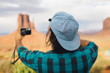 Rear view of young man taking selfie, Monument Valley, Arizona, USA