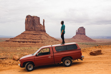 Young man looking out from top of four wheel drive, Monument Valley, Arizona, USA