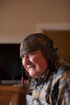 Senior man indoors, wearing old leather football helmet