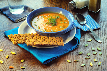 Pumpkin cream-soup. Pumpkin cream-soup. Hot pumpkin soup with toasted sesame seeds in a blue bowl on a wooden table. Still life with a bowl of soup, spoon, pumpkin seeds and slices of bread