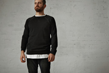 Bearded brutal hipster wearing a blank black longsleeve shirt with a white t-shirt underneath and black jeans against white brick wall background