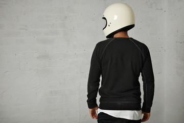 Back shot of a young man dressed in black and white casual clothes wearing a shiny white blank motorcycle helmet isolated on white