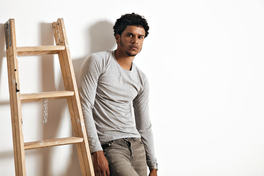 Serious sad muscular African American model in heather grey longsleeve cotton t-shirt and jeans leaning on a white wall next to a wooden stepladder