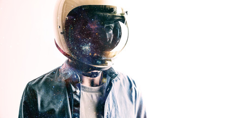 Futuristic portrait of a young man in a casual shirt and a white helmet with starry sky projected on the shield isolated on white Double exposure.