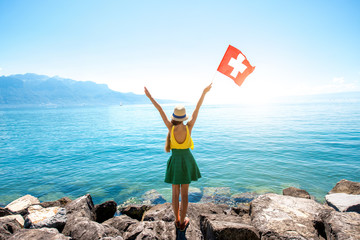 Young female traveler with swiss flag enjoying great view on Geneva lake in Switzerland