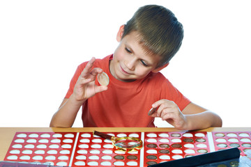 Boy examines coins from his collection isolated