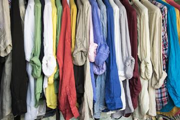 A rack of colorful shirts hanged for sale at the market.