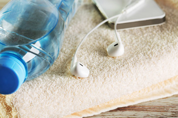 white headphones, phone and a bottle of water  on a terry towel