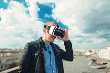 Confident young wearing a pair of VR glasses standing above the city on the rooftop building with the blue sky background excited by augmented reality