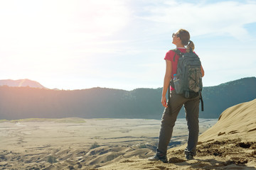 Happy young woman with a travel backpack enjoying sunrise at desert canyon