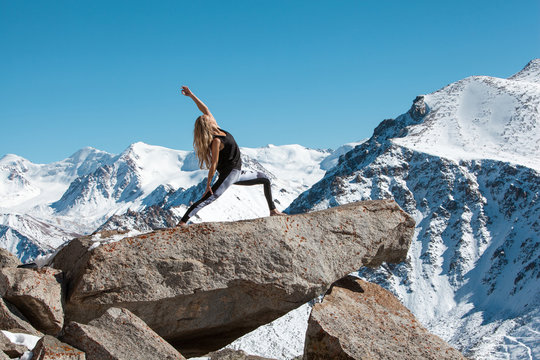 Woman is practicing yoga against Kazakhstan mountains.