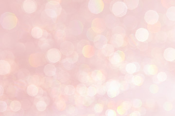 Bokeh soft pastel pink background with blurred golden lights. Festive background.