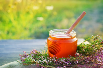 Honey in a glass jar with flowers melliferous herbs on a wooden surface. Honey with flowers of juniper