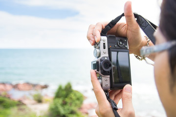 Hand holding a mirrorless digital camera prepare for take a landscape photo