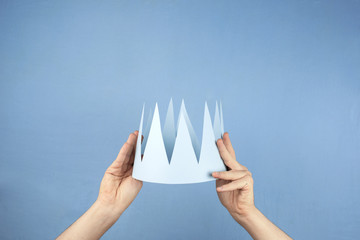 Escena minimalista de unas manos sujetando una corona, a punto de colocársela en la cabeza al futuro rey o reina