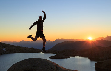 Fotomurales - Hiker jumping out of happiness during a clear sunset at a lake near Chamonix.