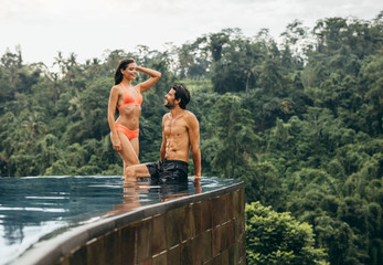 Happy young couple relaxing at edge of swimming pool