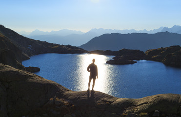 Fotomurales - Man looking over a lake, Lac Cornu, toward the sun.