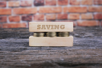 Business Concept - SAVING word Golden coin stacked with wooden