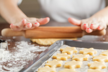 Woman baking ginger bread stars for Christmas. Natural Colors. R