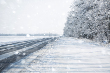 Winter road. Winter background. Drifts, snow, tire tread imprint. Copy space.
