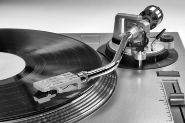 A vinyl record playing on a record player. Vinyl music being played on a turntable.
