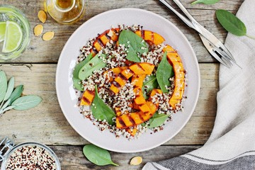 Quinoa salad with grilled pumpkin and fresh spinach on a rustic wooden table.Superfood and clean eating concept. Selective focus